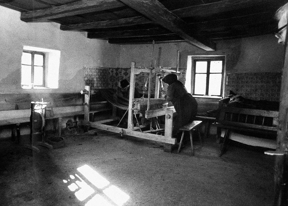 "Room where Felszeg Dance Events are held, with Klára Győri, ""Auntie Kali,"" weaving; 1967"