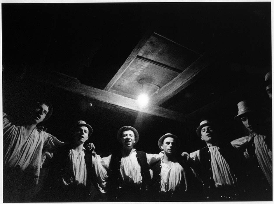 Young men sing in semi-circlular formation; 1970